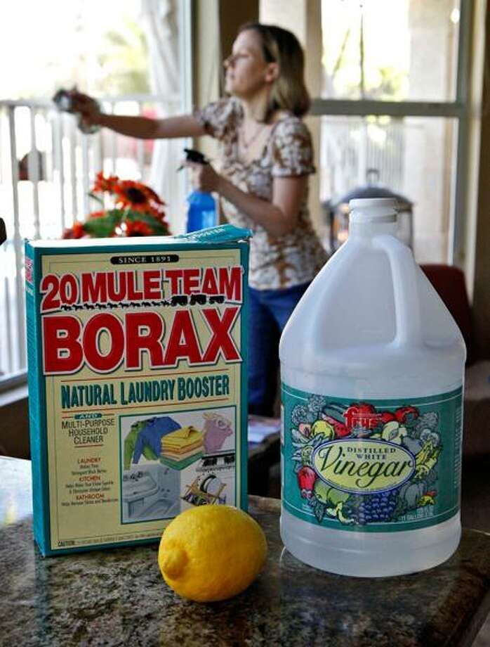 File photo shows Wendy Brooks as she cleans her windows with white vinegar and newspapers at her home in Phoenix. Brooks uses mostly Borax and vinegar for the majority of her household cleaning. Borax can also be used to clean toilets.  For an extra-strength cleaner, add vinegar to the borax. Photo: AP / AP2009