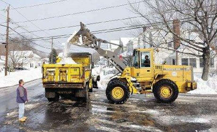 Hamden Public Works crews remove truckloads of snow from the corner of Collins Street and Circular Avenue Saturday. Mike Siciliano, superintendent of streets for the town, left, said the crews were clearing the piles on the corners so that people had a better line of sight when trying to pull into traffic. Driving the payloader is Rob Romandetti. (Peter Casolino/Register)