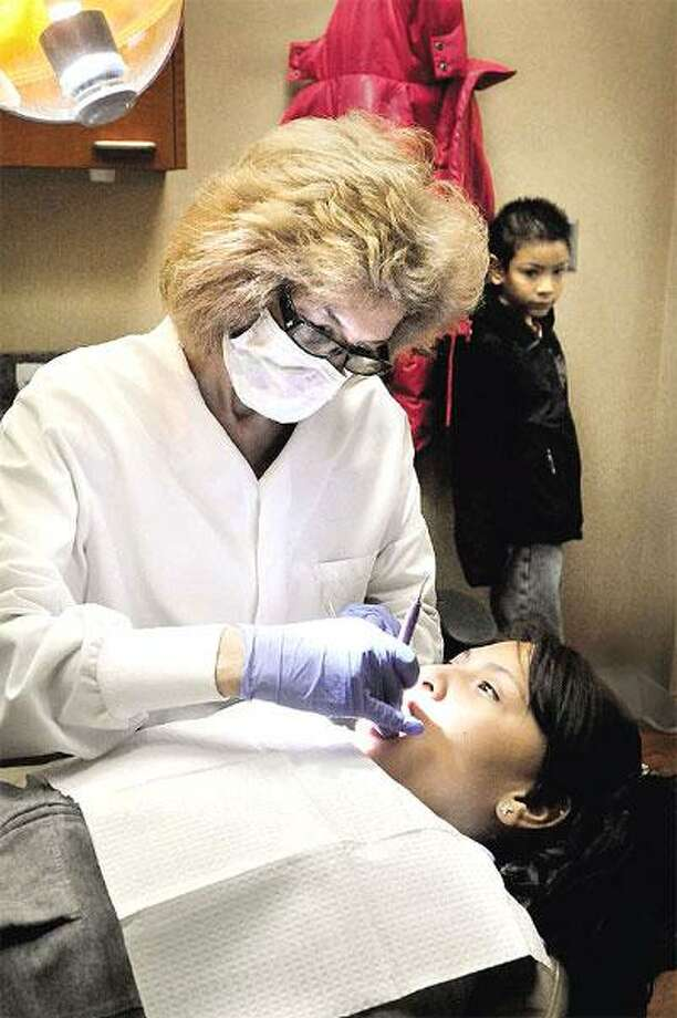 Peggy Dercole cleans New Haven resident Karen Barragan's teeth during Levy Dental Group's annual free dental care clinic Saturday in the city as her brother, Henrique, looks on. Services offered Saturday included screenings, cleanings, examinations, X-rays, fluoride treatments, sealants, extractions and fillings. The staff at Levy volunteered for the day as part of national Give Kids A Smile Day. (Melanie Stengel/Register)