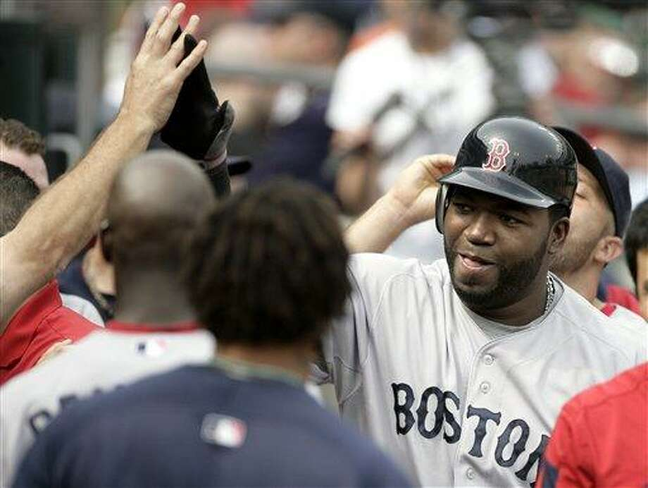 Boston Red Sox's David Ortiz, right, is congratulated in the dugout after hitting a solo home run in the ninth inning of the first baseball game of a doubleheader on Sunday, May 29, 2011, in Detroit. The Red Sox defeated the Tigers 4-3. (AP Photo/Duane Burleson) Photo: AP / FR38952 AP