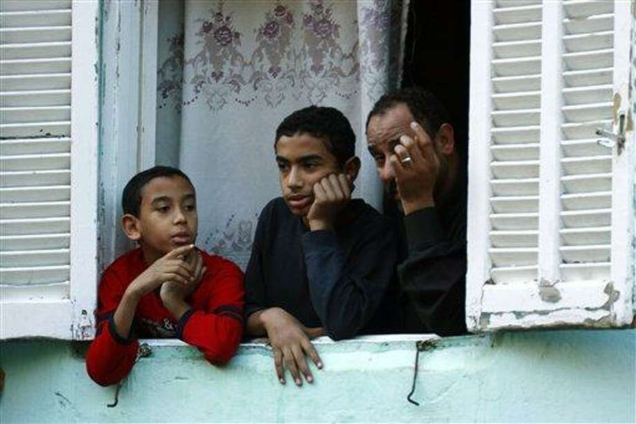 Egyptians peer from their home's window in Cairo, Egypt, Sunday, Jan. 30, 2011. With the police having disappeared from the streets, residents reported gangs of youths, some on motorbikes, roaming the streets, looting supermarkets, shopping malls and stores. Some of the gangs made it to affluent residential areas in the suburbs, breaking into luxury homes and apartments. The crackle of gunfire could be heard in the city center as well as outlying districts. (AP Photo/Amr Nabil) Photo: AP / AP