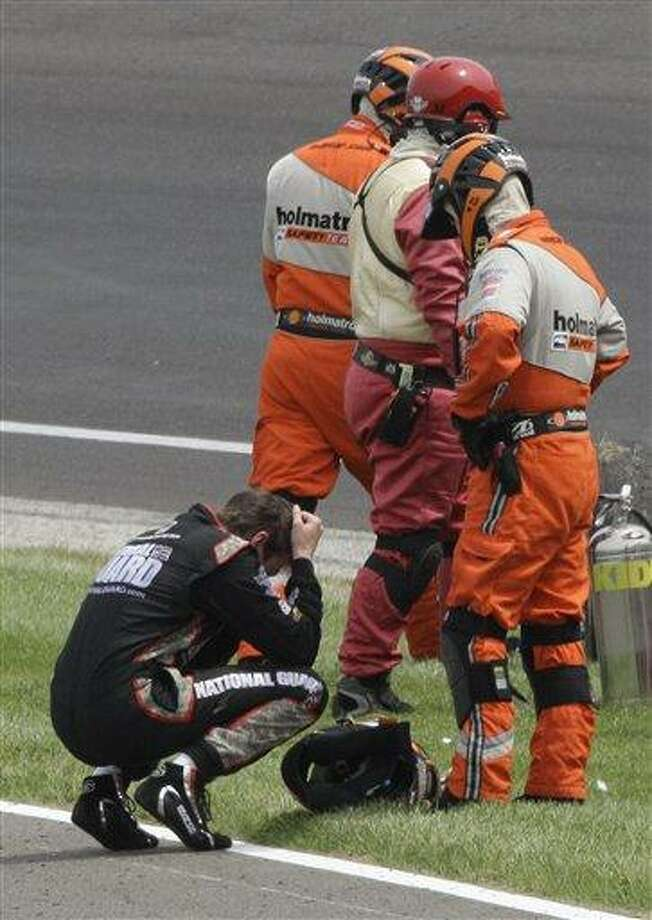 IndyCar driver JR Hildebrand reacts next to track safety personnel after he crashed on the final lap of the Indianapolis 500 auto race at the Indianapolis Motor Speedway in Indianapolis, Sunday, May 29, 2011. Dan Wheldon, of England, won the race. (AP Photo/Paul Sancya) Photo: AP / AP