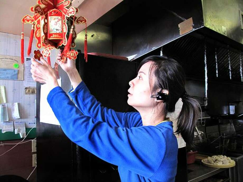 DEBBI MORELLO/ The Register Citizen Vivian Wang, owner of the New China Star in Torrington, describes one of the decorations in the restaurant to celebrate the Chinese New Year. The Year of the Dragon began last Monday and runs until February 6.