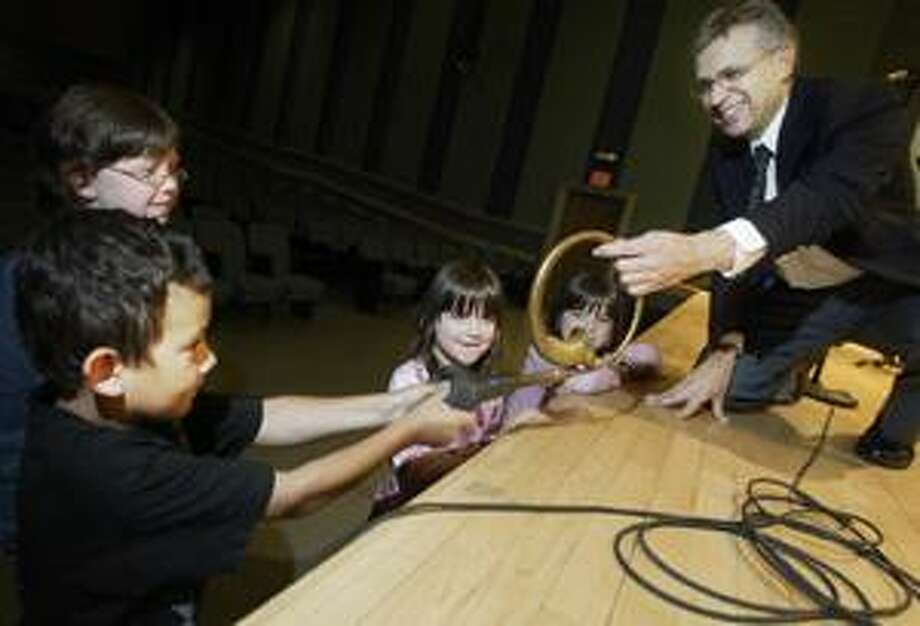 Dispatch Staff Photo by JOHN HAEGER Syracuse Symphony Percussion Ensemble member Ernie Muzquiz holds a klaxon horn as Nick Shrader, 7, squeezes it while Erin Garrison, 10, Claire Garrison, 6, and Anna Garrison, 6, look on before the start of the concert at Oneida High School on Friday, July 20, 2007.