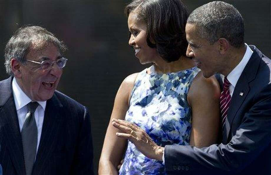 From right, President Barack Obama, first lady Michelle Obama, and Secretary of Defense Leon Panetta talk on stage at the end of a  Memorial Day ceremony at the Vietnam Veterans Memorial Wall to commemorate the 50th anniversary of the Vietnam War, Monday, in Washington.  Associate Press Photo: AP / AP