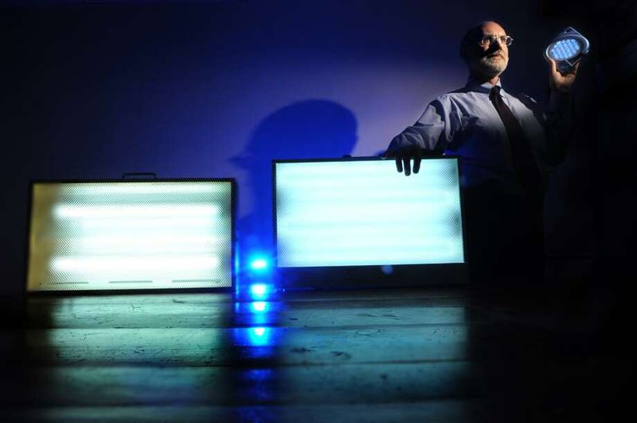 Peter Hvizdak/Register photo: Dr. Paul Desan, director of the Winter Depression Research Clinic at the Yale School of Medicine, has created a more portable light box, upper right. At left are the more conventional models on the market. / PETER HVIZDAK