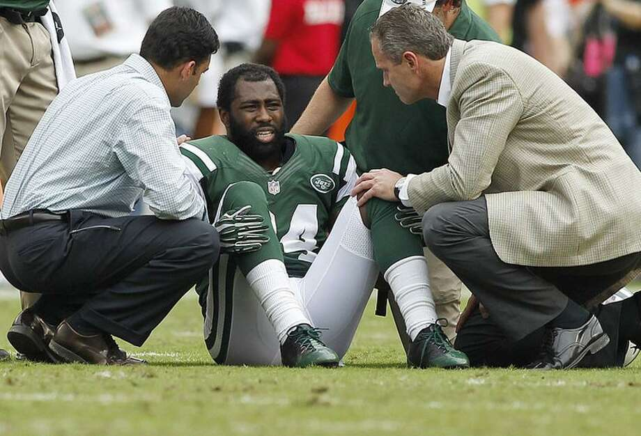 New York Jets cornerback Darrelle Revis (24) is  attended to after being injured in the second half in a game against the Miami Dolphins at Sun Life Stadium. (Robert Mayer-US PRESSWIRE) Photo: US PRESSWIRE / Robert Mayer