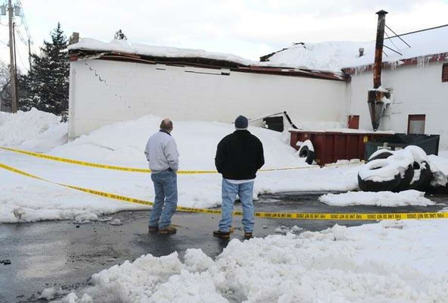 Steve Smith and John Russo of United Cleaning and Restoration look at damage to the Tri State Tire building on Dudley Avenue in Wallingford Thursday after a portion of the roof collapsed. (Brad Horrigan/Register)