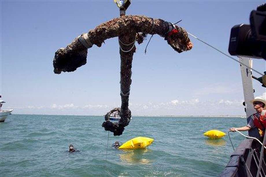 A 3,000 pound anchor from what is believed to be the wreck of the pirate Blackbeard's flagship, the Queen Anne's Revenge, is recovered from the ocean where it has been since 1718, on Friday, May 27, 2011 in Beaufort Inlet, in Carteret County  N.C. Crew member Mitchel Gilliland, right, helps guide the anchor aboard the Dan K. Moore.  (AP Photo/The News & Observer, Robert Willett) Photo: AP / 2011 The News & Observer
