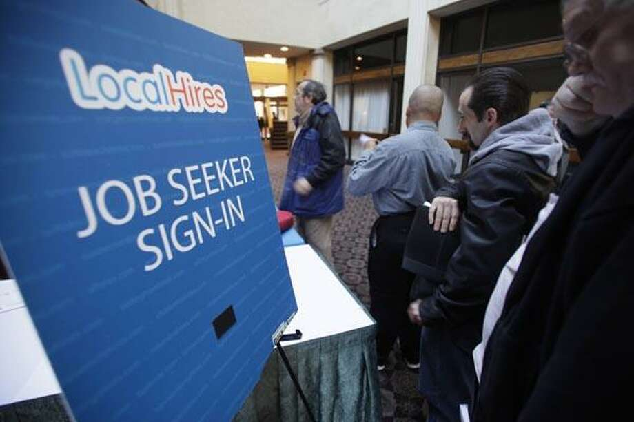 In this Jan. 26, 2011 photo, job seekers line up for a job fair at a hotel in Dallas. The number of people applying for unemployment benefits rose sharply last week, but the figures were largely distorted by rare snowstorms that swept through the Southeast, The Associated Press reports Thursday, Jan. 27, 2011. (AP Photo/LM Otero) Photo: AP / AP