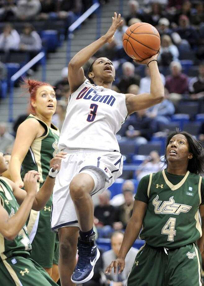 Connecticut's Tiffany Hayes, center, drives past South Florida's Caitlin Rowe, left, and Tiffany Conner (4) during the first half of an NCAA college basketball game in Hartford, Conn., on Saturday, Jan. 28, 2012. (AP Photo/Fred Beckham) Photo: AP / FR153656 AP
