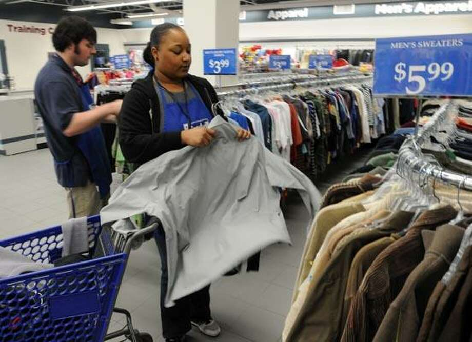Sean Fenton of Milford, left, and Candace Phillips of Stratford put out clothes for sale at the new Goodwill store in Milford. Mara Lavitt/Register