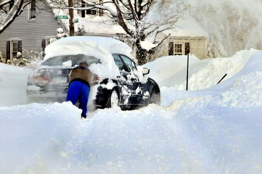 John Baltazar helps a neighbor whose car car is stuck on Frederick Street in New Haven.    Melanie Stewngel/Register