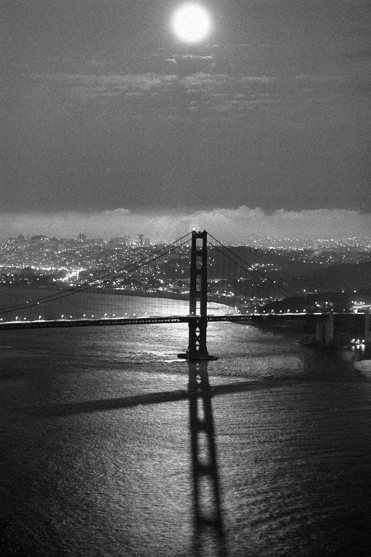 The moon shines down on the Golden Gate Bridge in San Francisco, Monday, July 6, 1982 on the night of the lunar eclipse. It was the longest total lunar eclipse of the century which began at 10:22 p.m. PDT. In the background is the San Francisco skyline. (AP Photo/Paul Sakuma)