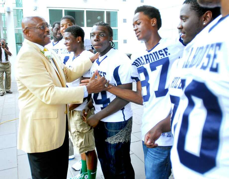 Football legend and former James Hillhouse High School football player Floyd Little, left, meets current Hillhouse football players at the New Haven Athletic Center in New Haven, which was renamed the Floyd Little Athletic Center in his honor Thursday. Shaking hands with Little is Shakiem Wilson. Arnold Gold/Register