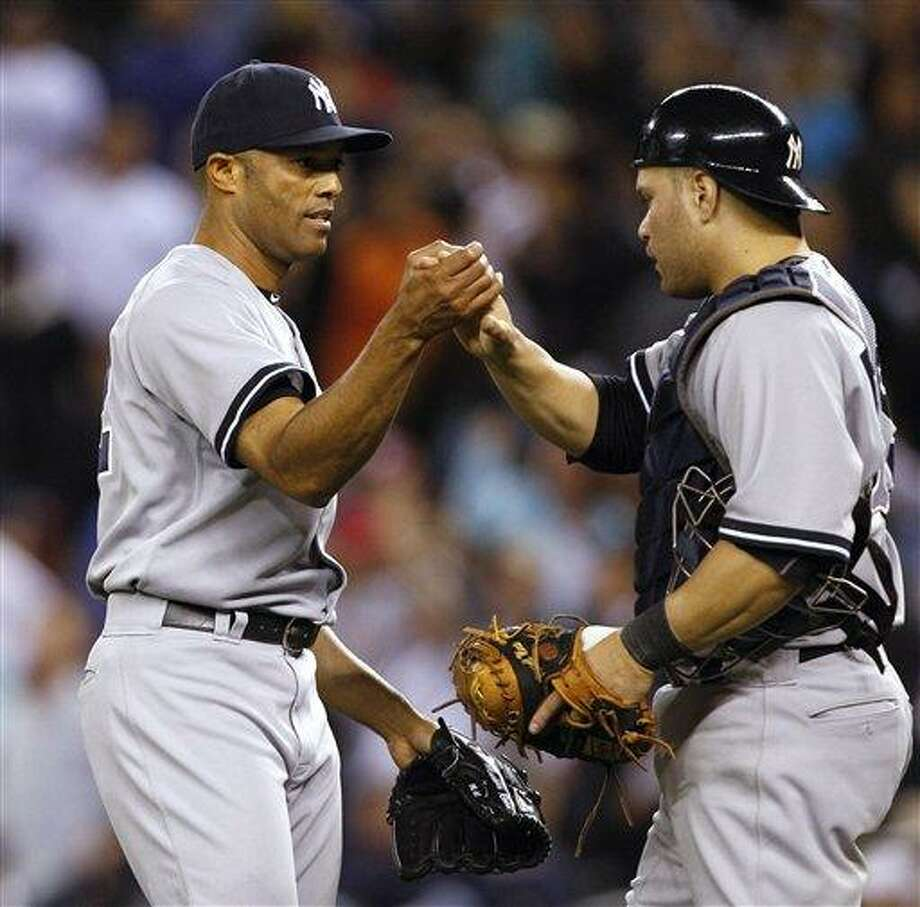 New York Yankees closer Mariano Rivera, left, is greeted by catcher Russell Martin after the team beat the Seattle Mariners in a baseball game Tuesday, Sept. 13, 2011, in Seattle. The Yankees won 3-2.  It was Rivera's 599th save. (AP Photo/Elaine Thompson) Photo: AP / AP