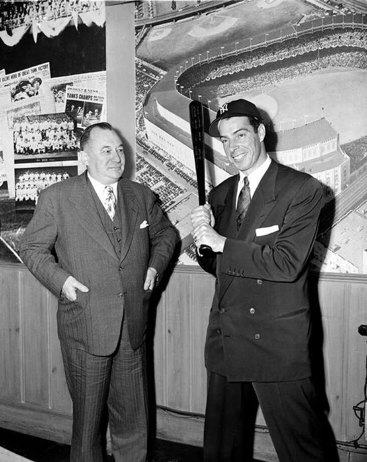 Yankees outfielder Joe DiMaggio brandishes his bat after signing his 1950 contract at the Yankees office in New York, January 24, 1950. At left is Yankees General Manager George Weiss. (AP Photo) Photo: ASSOCIATED PRESS / AP1950