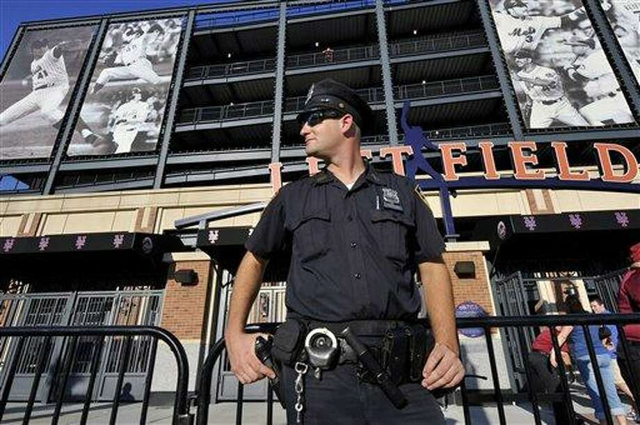 A New York City Police officer stands outside Citi Field as fans enter the stadium before a baseball game between the New York Mets and the Chicago Cubs, Friday, Sept. 9, 2011, at Citi Field in New York. Security has been enhanced around the country in the weeks leading up to the 10th anniversary of the Sept. 11 attacks. (AP Photo/Kathy Kmonicek) Photo: AP / FR170189 AP