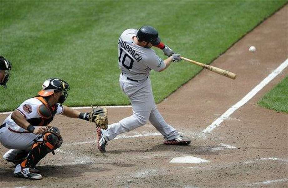 Boston Red Sox's Kelly Shoppach (10) bats during a MLB baseball game against Baltimore Orioles catcher Luis Exposito, left, Wednesday, May 23, 2012, in Baltimore. The Red Sox won 6-5. (AP Photo/Nick Wass) Photo: AP / FR67404 AP