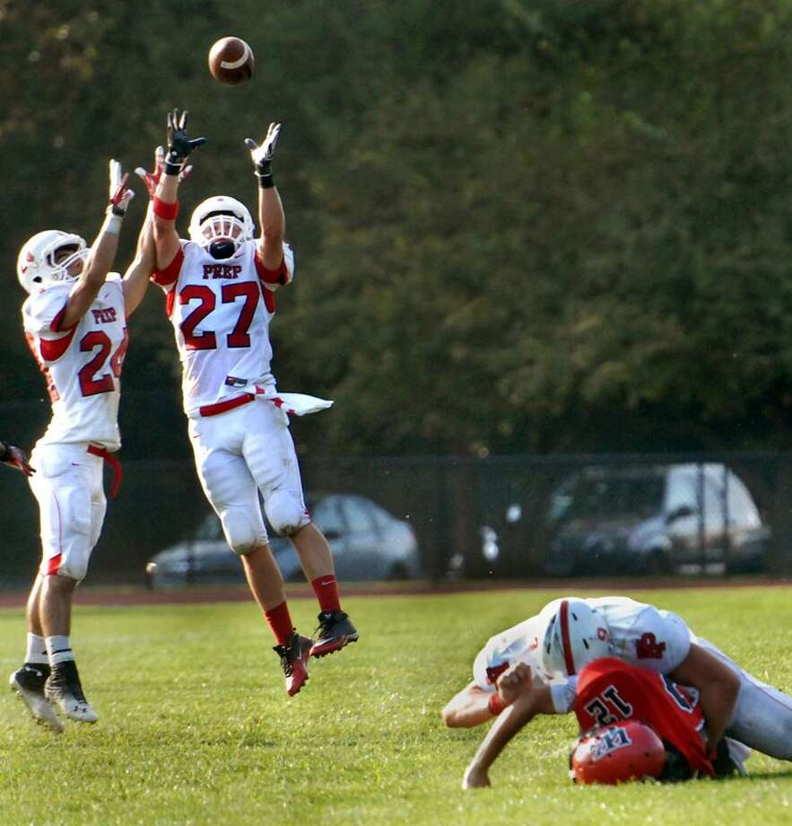 A.J. Consiglio of Wilbur Cross is tackled, but not before he throws an interception to Fairfiueld Prep's Matthew Montani in the second quarter of Prep's 47-0.    Melanie Stengel/Register