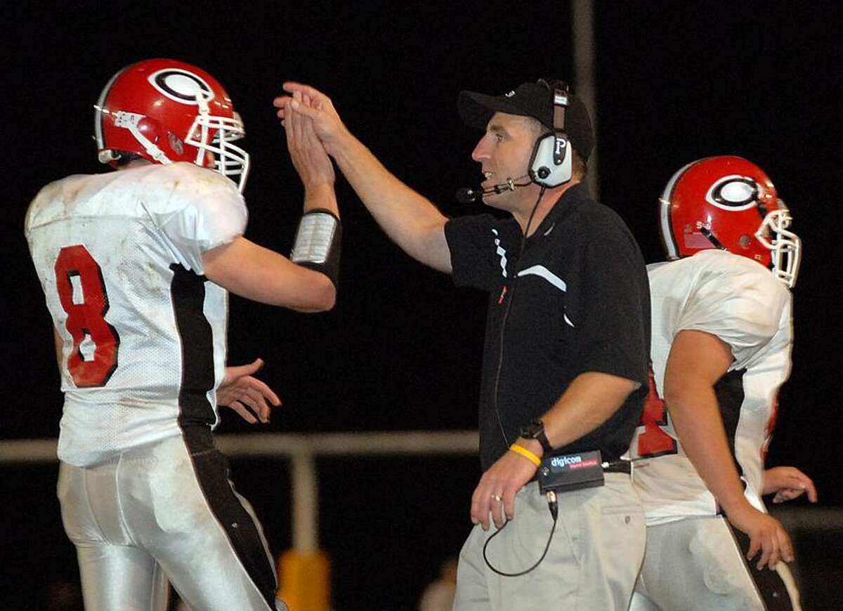 Reg0670 Photo-Peter Casolino 07/28/06Madison-- Cheshire coach Mark Ecke high fives QB Billy Ragone after Cheshire scored their third touchdown in the first half . Peter Casolino