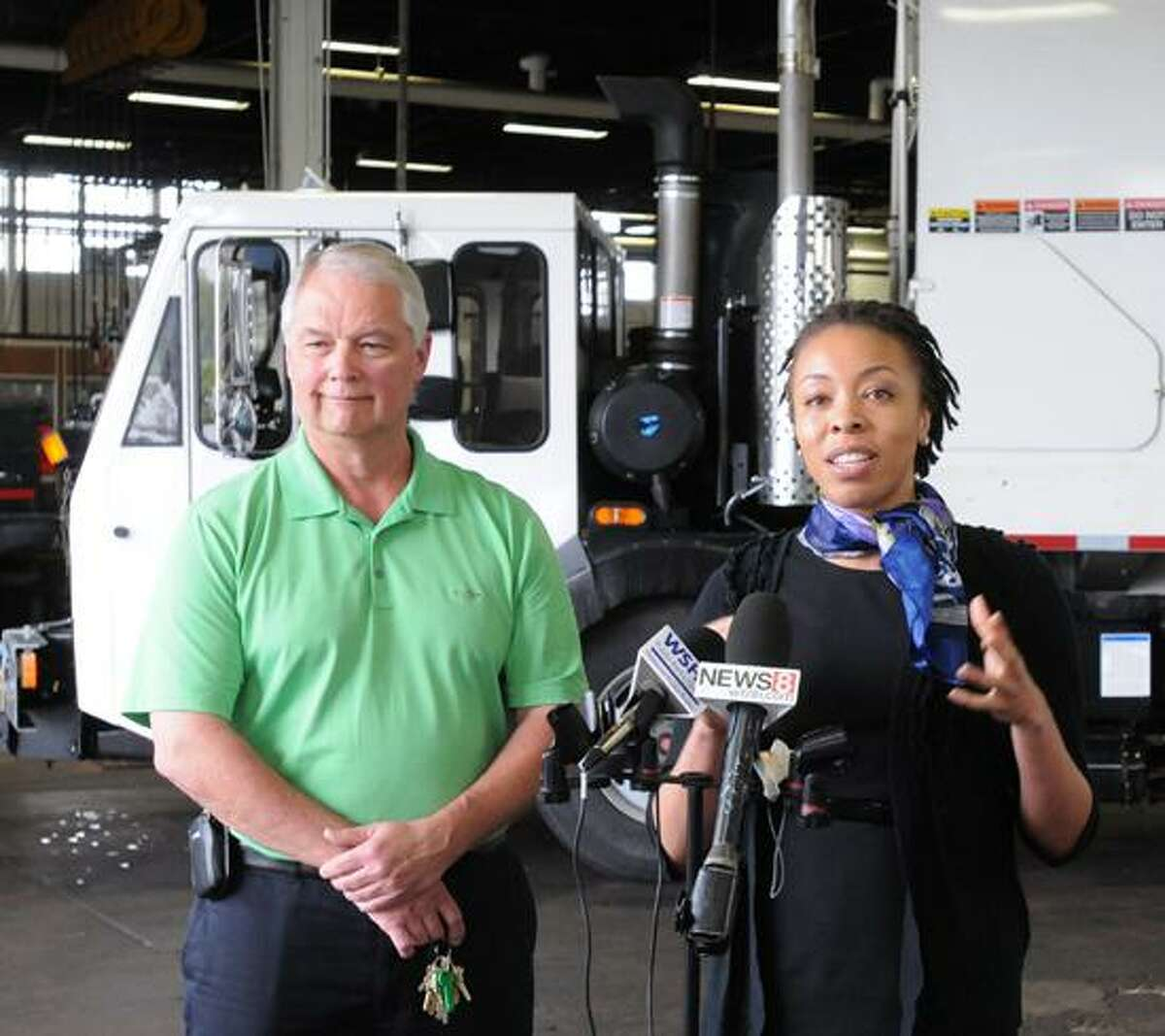 John Prokop, director of the New Haven Public Works Department, left, and Dr. Chisara N. Asomugha, city of New Haven community services administrator, right, unveiled six trucks retrofitted with diesel exhaust filters during a press conference at DPW headquarters Tuesday. The new filters will result in a 95 percent reduction in particulate emissions, a contributor to asthma. The diesel exhaust filters are shown on a truck at rear. Peter Hvizdak/ New Haven Register