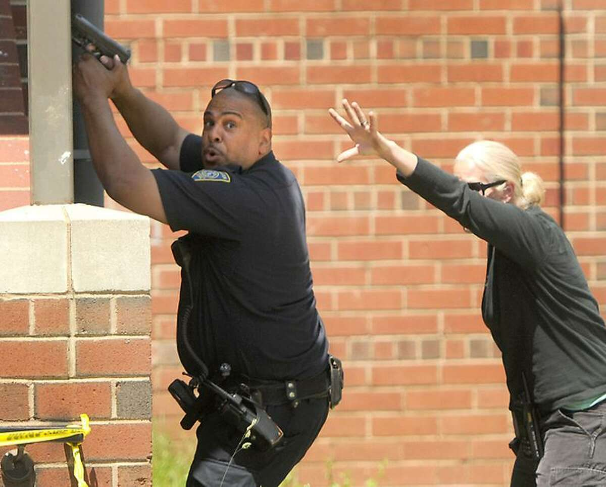 New Haven Police draw their guns after police came upon a stabbing while investigating a shooting at 184 Hamilton St., in the Farnam Courts housing project in New Haven Friday. Peter Hvizdak/ New Haven Register