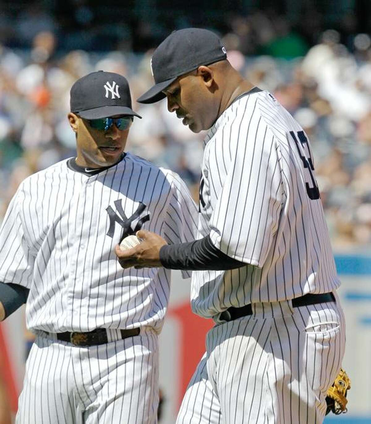 New York Yankees second baseman Robinson Cano, left, stands beside Yankees starting pitcher CC Sabathia in seventh inning of their 5-2 loss to the Cincinnati Reds in an interleague baseball game at Yankee Stadium in New York, Sunday, May 20, 2012. Sabathia walked in the go-ahead run in the loss. (AP Photo/Kathy Willens)