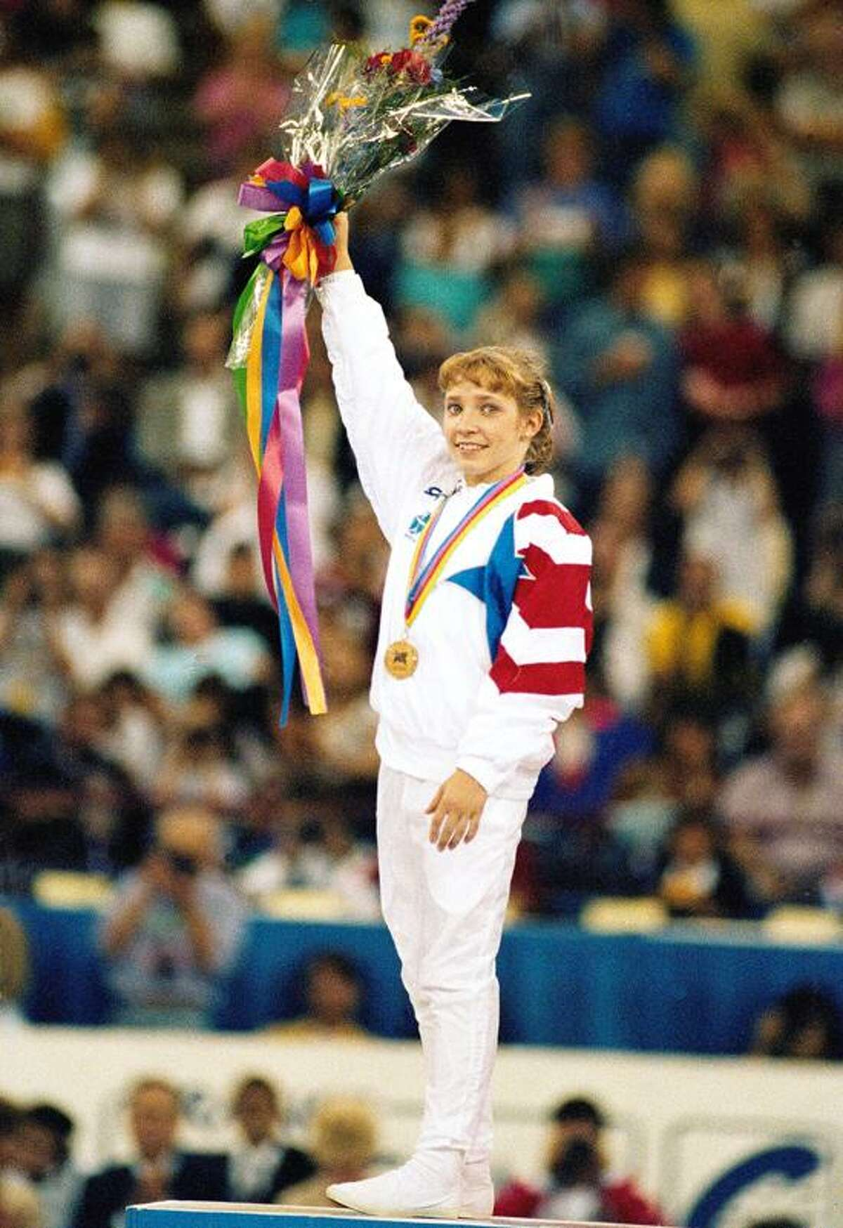 FILE - United State's Kim Zmeskal holds up flowers during the medal ceremony after winning the gold medal in the women's all around at the World Gymnastics competition in Indianapolis. Zmeskal's 1991 world title set the stage for the