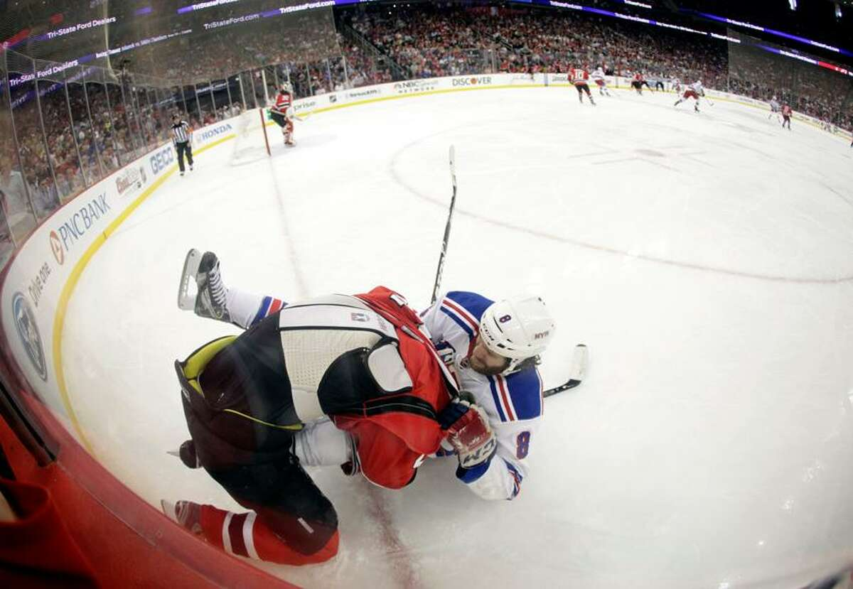 In this image made with a fisheye lens, New Jersey Devils defenseman Anton Volchenkov, top, of Russia, and New York Rangers' Brandon Prust wrestle in the corner during the first period of Game 3 of an NHL hockey Stanley Cup Eastern Conference final playoff series Saturday, May 19, 2012, in Newark, N.J. (AP Photo/Julio Cortez)
