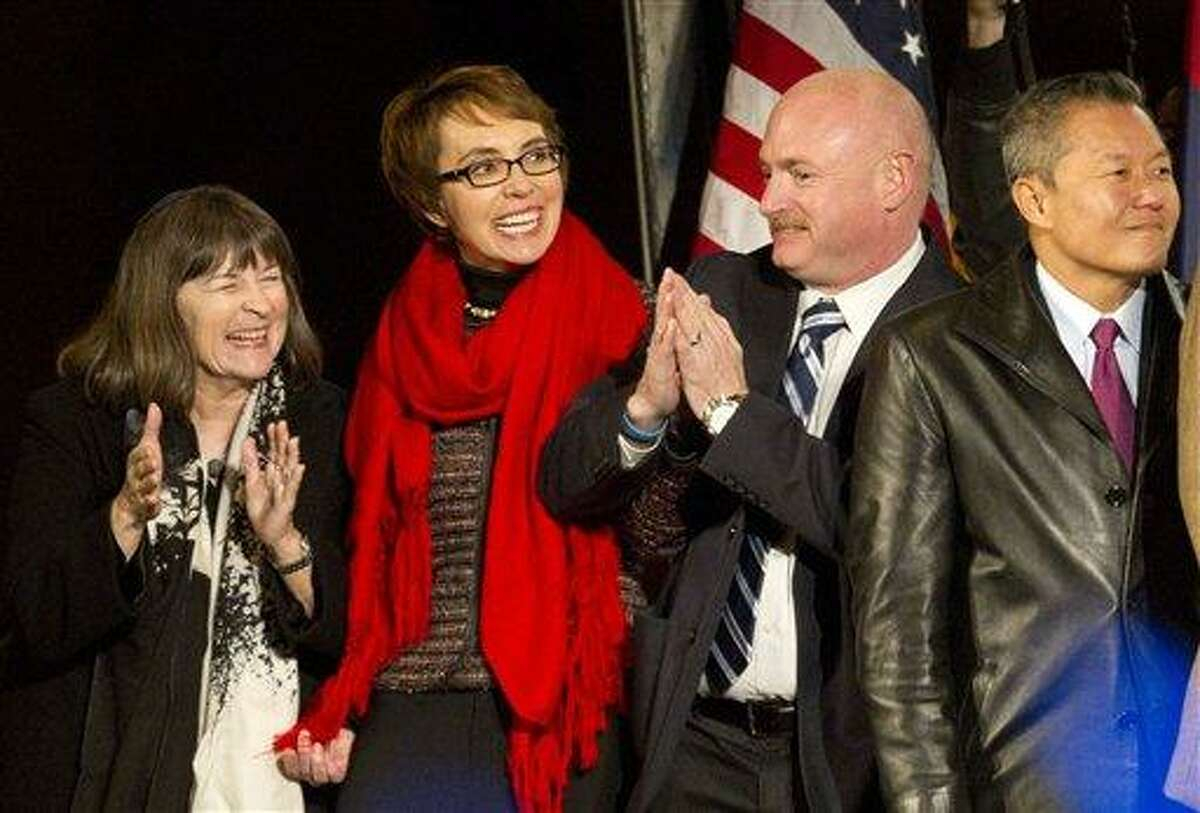From left, Rabbi Stephanie Aaron, U.S. Rep. Gabrielle Giffords, her husband Mark Kelly, and University of Arizona Medical Center's Dr. Peter Rhee, dance to the music of Calexico, during a vigil at the University of Arizona in Tucson, Ariz., on Jan. 8. Giffords led a crowd in the Pledge of Allegiance in a rare public appearance one year after surviving a deadly shooting. Associated Press
