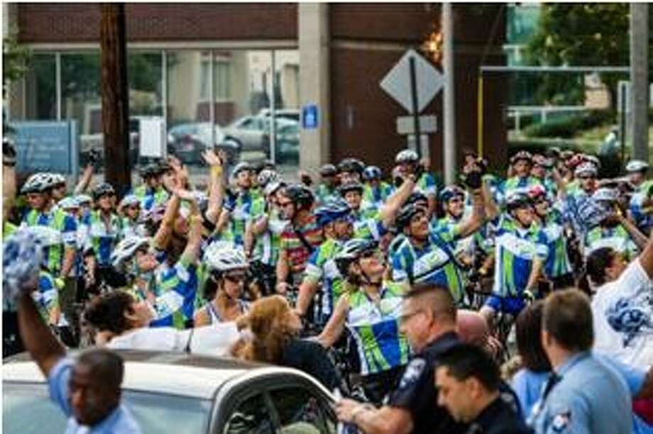 Riders stop to wave at patients at Smilow Cancer Hospital at Yale-New Haven after setting out from the Yale Bowl Saturday for the 2nd annual Closer to Free Ride.