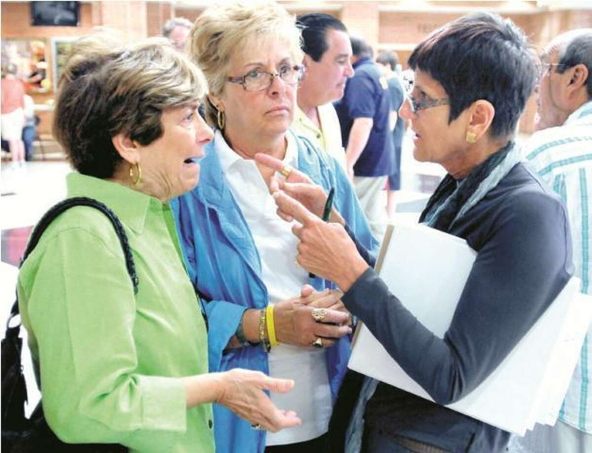 Barbara Bucci, left, and Cynthia Fucci, center, owners of the Beachhead Restaurant in the Cosey Beach section of East Haven, talk with U.S. Rep. Rosa DeLauro, D-3, during a Help Fair at East Haven High School Saturday. Arnold Gold/Register
