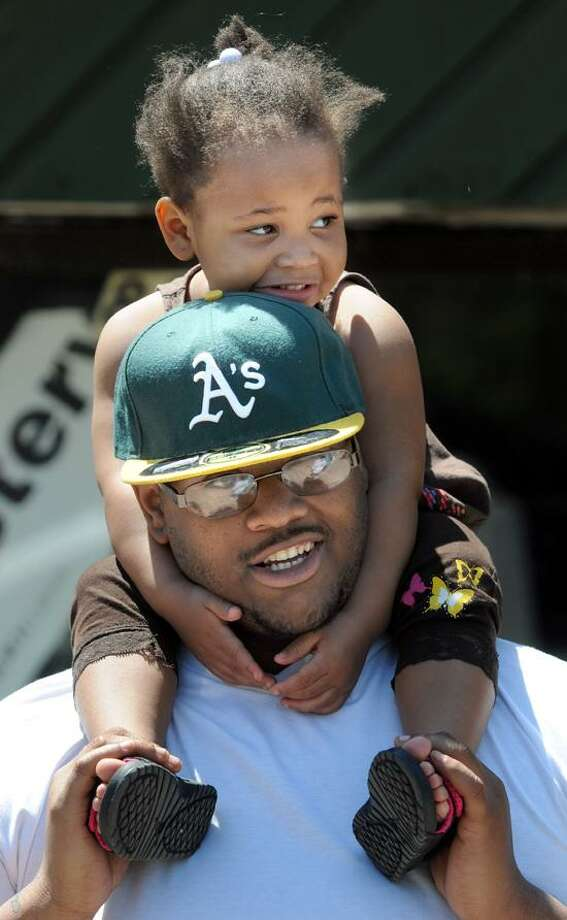 Carrington Williams of New Haven and his daughter Ashiya age 3 at the side of the parade route. Mara Lavitt/New Haven Register