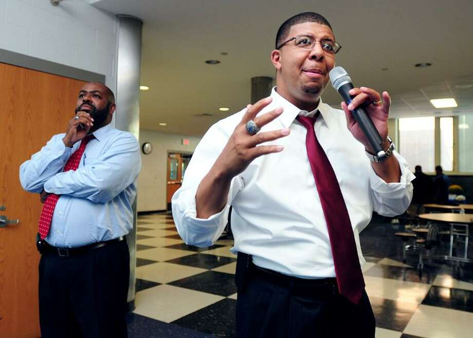 Attorney Michael Jefferson, left, listens to his client, Hillhouse High School Principal Kermit Carolina, right, speak at a meeting concerning a grade tampering investigation at the Hillhouse High School cafeteria in New Haven. Photo by Arnold Gold/New Haven Register