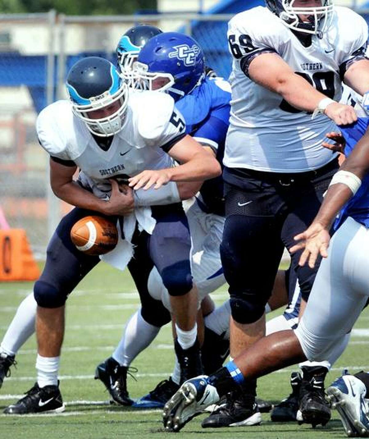 SCSU quarterback Kevin Lynch (left) fumbles the ball while being tackled in the second half against CCSU in New Britain on 9/3/2011. Lynch recovered the ball.Photo by Arnold Gold/New Haven Register AG0423B