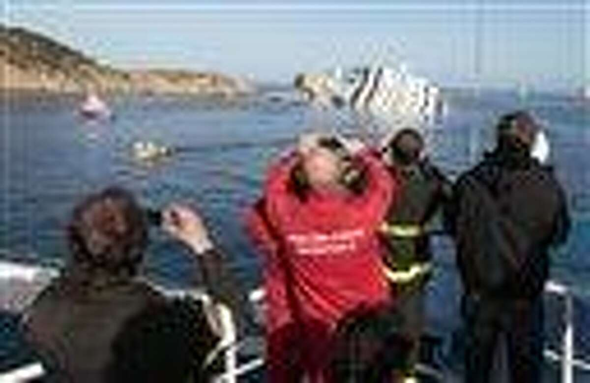 Firefighters take pictures of the cruise ship Costa Concordia ship, off the Tuscan island of Giglio, Italy, Saturday. The cruise captain who grounded the Costa Concordia off the Tuscan coast with 4,200 people on board did not relay correct information either to the company or crew after the ship hit rocks, the cruise ship owner's CEO said as the search resumed for 21 missing passengers. Associated Press