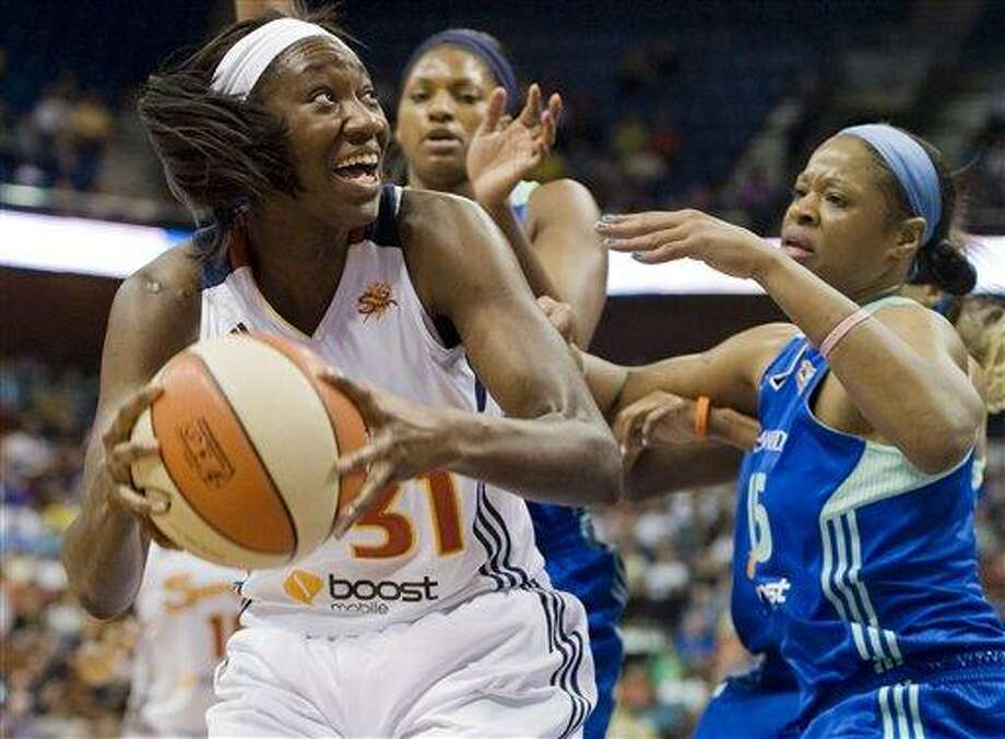 Connecticut Sun's Tina Charles, left, is guarded by New York Liberty's DeMya Walker, rear, and Kia Vaughn, right, during a WNBA basketball game in Uncasville, Conn., Sunday, May 20, 2012. Charles led Connecticut with 25 points as the Sun won 92-77. (AP Photo/Jessica Hill) Photo: AP / AP2012
