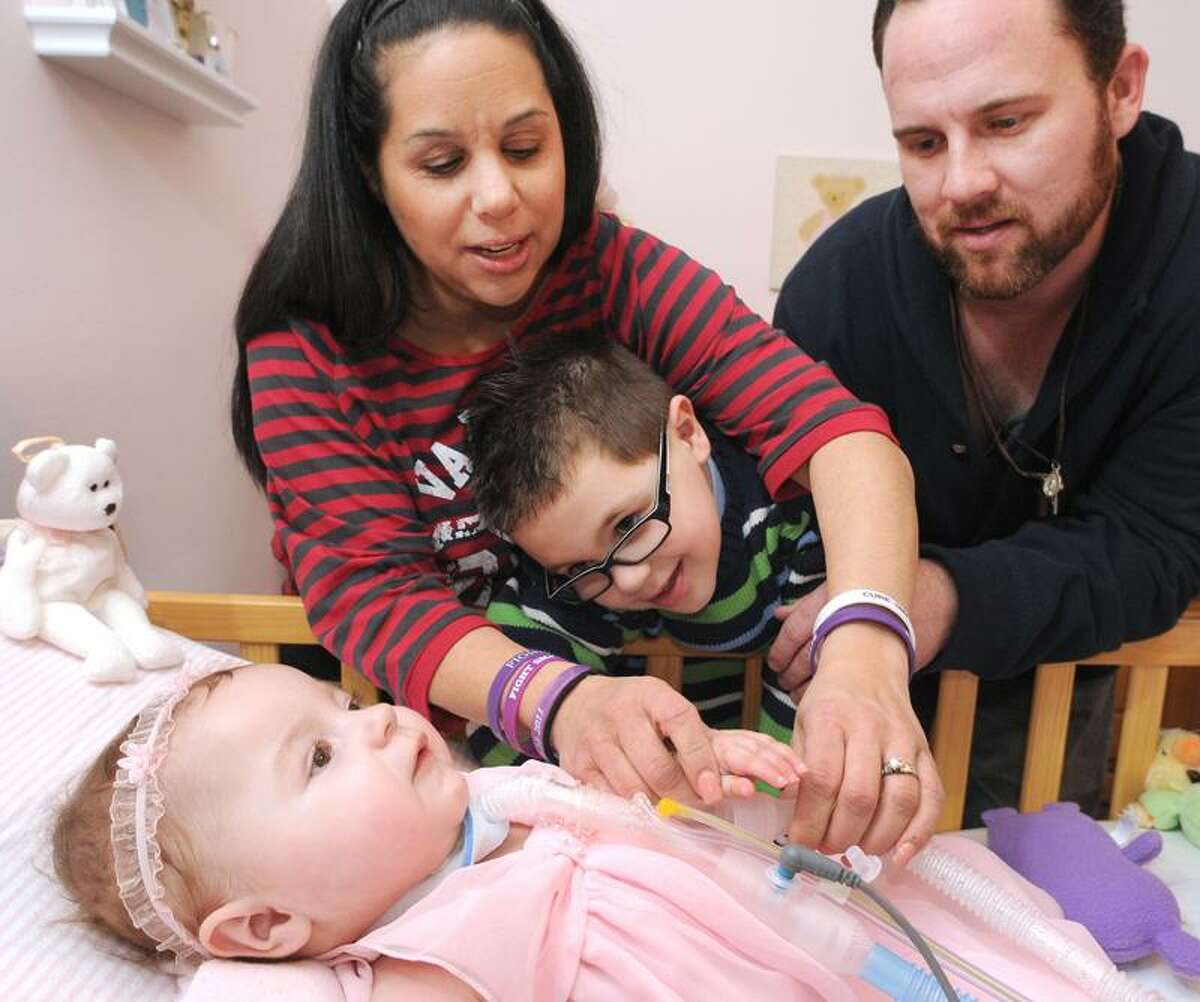 Peter Hvizdak/Register: Eva Grace Kelly, 1, with her brother Noah, 6, and parents, Melissa and John Kelly, in their West Haven home.