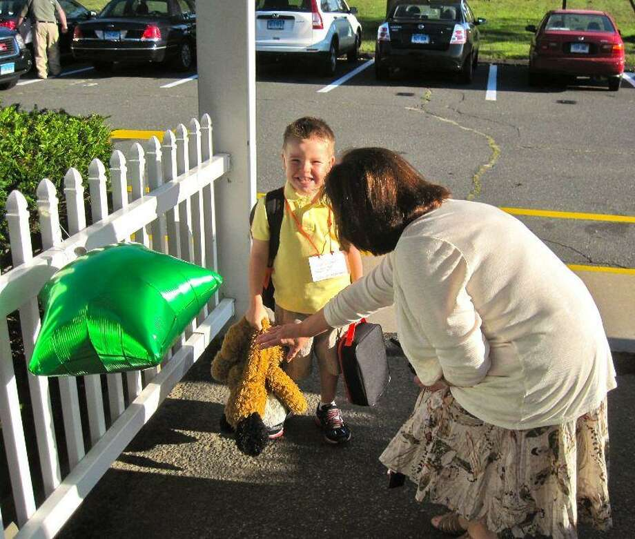 Christine DiGrazia, principal of Bradley School in Derby, greets kindergartner Carson Sisbarro, 4, on the first day of school Wednesday. Patricia Villers/Register
