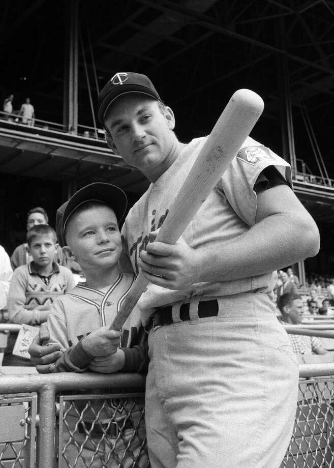 This Sept. 12, 1964, file photo shows Minnesota Twins' Harmon Killebrew  posing with 9-year-old Johnny Guiney, at New Yorks Yankee Stadium. Killebrew had visited Guiney in May after he was hospitalized with critical burns suffered when his altar boy robes caught fire. Johnny asked his idol to hit a homer, and the leading home run hitter in the major leagues responded with a first inning, two-run blast. Killebrew, the Twins slugger known for his tape-measure home runs, died Tuesday, May 17, 2011, at his home in Scottsdale, Ariz. He was 74. (AP Photo/Harry Harris, File) Photo: AP / Copyright 2011 The Associated Press. All rights reserved. This material may not be published, broadcast, rewritten or redistributed.