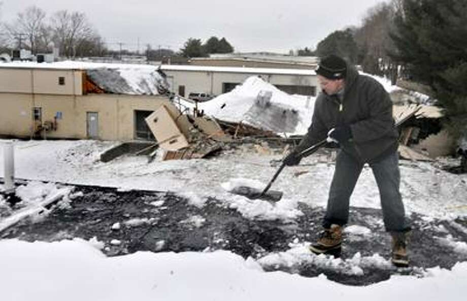 MILFORD ____Tim Jackson,of Newtown, shovels the snow from the roof of Premier Kitchens and Woodworking LLC.  The building is next door to Atlantic Powder Coating, which collapsed.  Jackson dsays he believes that they were designed by the same architect.    Melanie Stengel/REgister