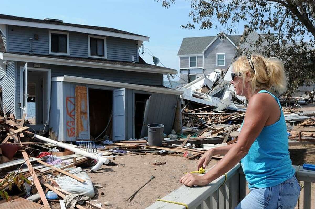 Roberta Sabo looks out from her back porch along Cosey Beach Avenue in East Haven Thursday. Sabo watched the houses behind hers get destroyed during the storm. Peter Casolino/Register