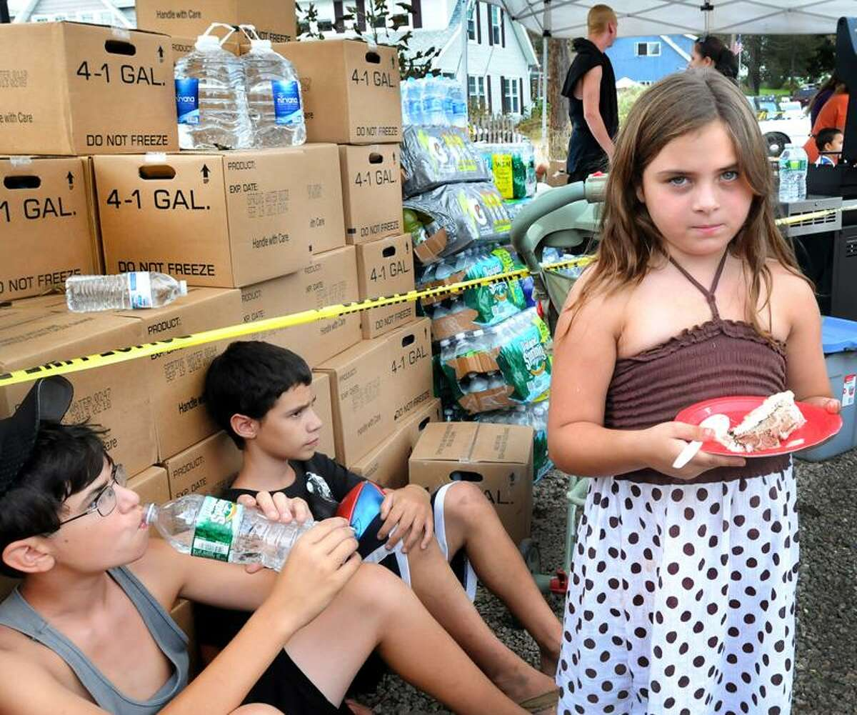 David Raziunas,12, and Chad Camposano,13, relax against boxes of donated food and water at the Cosey Beach