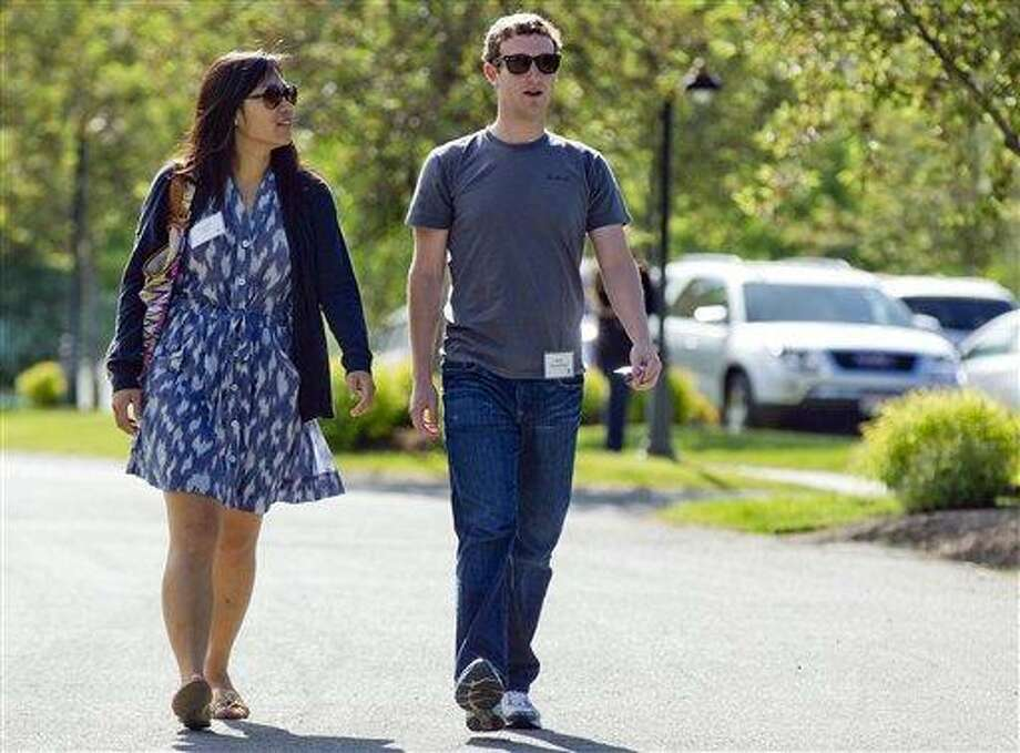 FILE- In this July 9, 2011, file photo, Mark Zuckerberg, president and CEO of Facebook, walks to morning sessions with his girlfriend Priscilla Chan during the 2011 Allen and Co. Sun Valley Conference, in Sun Valley, Idaho.  On Saturday, May, 19, 2012,  Zuckerberg and Chan tied the knot at a small ceremony at his Palo Alto, Calif., home, capping a busy week for the couple (AP Photo/Julie Jacobson) Photo: AP / 2011 AP