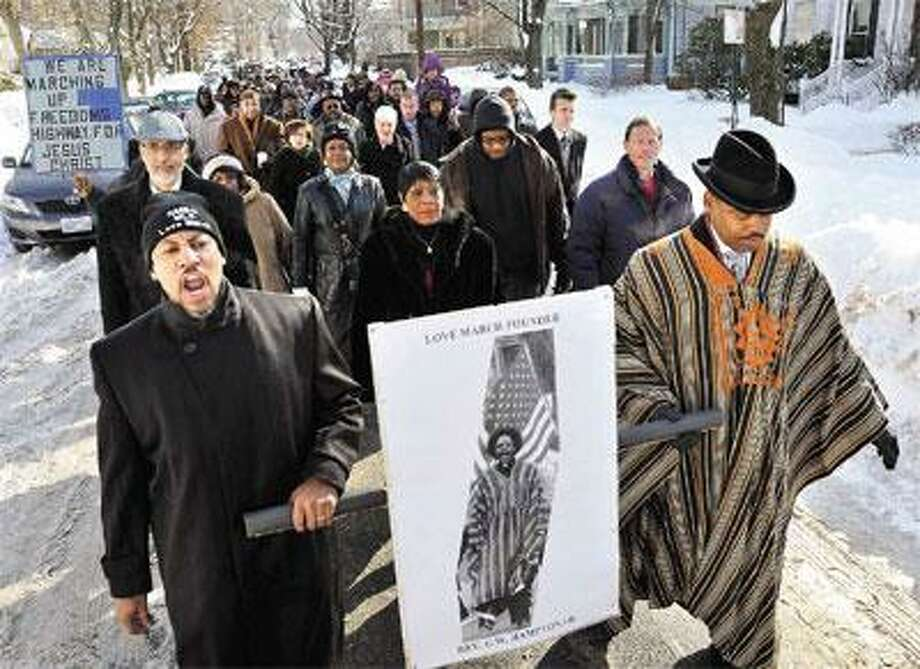 The Rev. Kennedy Hampton, left, and his brother, the Rev. Gerald Hampton, lead the annual Love March down Lawrence Street in New Haven Saturday. (Peter Casolino/Register)
