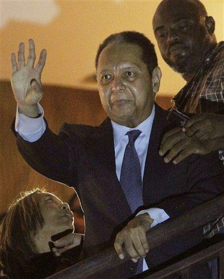 """Haiti's former dictator Jean-Claude """"Baby Doc"""" Duvalier, center, waves to supporters from a hotel balcony after his arrival in Port-au-Prince, Haiti, Sunday Jan. 16, 2011. Duvalier returned Sunday to Haiti after nearly 25 years in exile, a surprising and perplexing move that comes as his country struggles with a political crisis and the stalled effort to recover from last year's devastating earthquake. (AP Photo/Dieu Nalio Chery) Photo: AP / AP"""