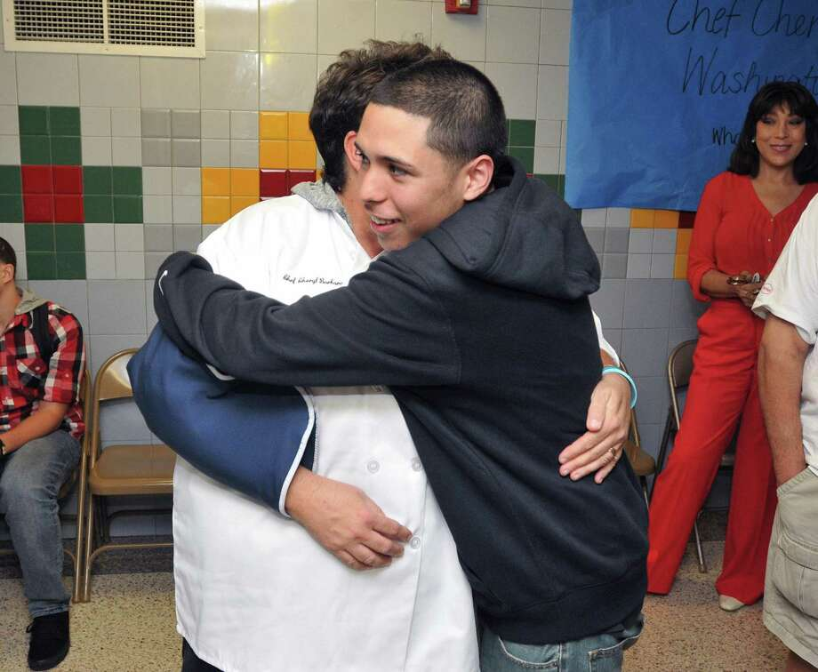 "New Haven-- Cheryl Barbara, High School in the Community school chef, gets a hug from Jaylin Santana (a Jr), as she prepares to leave to visit the White House. Barbara won the ""Chopped"" competition on the Food Network last year. Next to her, right, is her husband, John Barbara. Peter Casolino/New Haven Register 9/05/12"