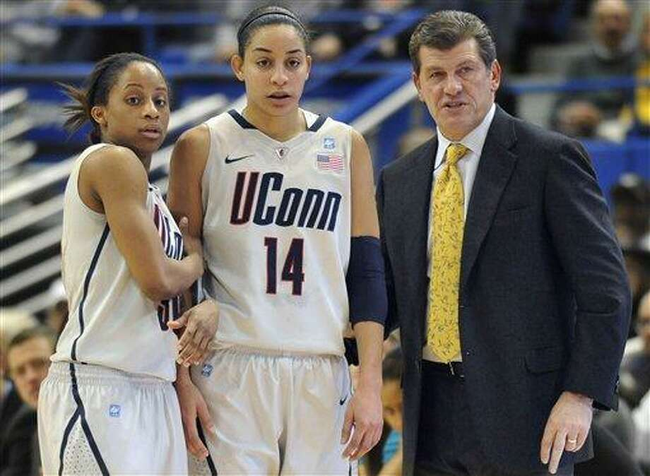 Connecticut head coach Geno Auriemma, right, talks with players Lorin Dixon, left, and Bria Hartley (14) during first half of an NCAA college basketball game against Louisville, in Hartford, Conn., Saturday, Jan. 15, 2011. (AP Photo/Jessica Hill) Photo: AP / AP2011
