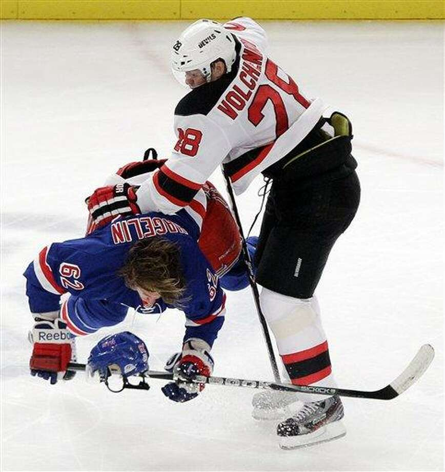 New Jersey Devils' Anton Volchenkov (28) and New York Rangers' Carl Hagelin (62) collide during the second period of Game 2 of the NHL hockey Stanley Cup Eastern Conference final playoff series, Wednesday, May 16, 2012, in New York. (AP Photo/Frank Franklin II) Photo: AP / AP